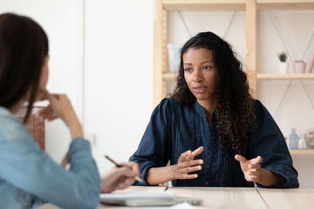 Photo pour Confident African American woman candidate speaking at job interview, answering hr manager employer questions, diverse business partners colleagues discussing project strategy, sharing ideas - image libre de droit