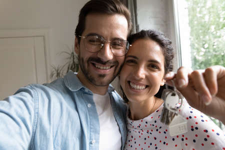 Close up self-portrait of happy young Caucasian couple buyers renters show house keys moving relocating to new home together. Selfie of smiling family tenants buy dwelling. Realty, relocation concept.