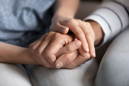 Photo pour Close up of millennial woman grown daughter, grandchild or younger friend holding tight hand of old mother, grandmother, elder relative or colleague helping to overpass life problems - image libre de droit