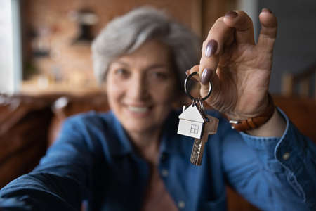 Close up blurred of happy elderly 60s grandmother show keys excited about house bank mortgage or lease, smiling mature woman tenant renter overjoyed to be home owner, relocation, rental concept