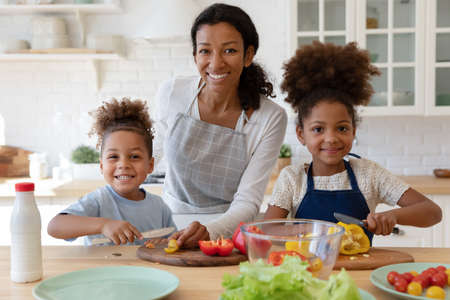 Photo pour Portrait of happy young african american mother enjoying cooking healthy vegetarian food together with joyful little cute children in modern kitchen, smiling adorable family looking at camera. - image libre de droit