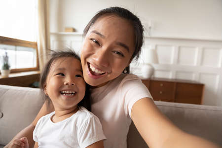 Photo for Close up head shot portrait smiling Asian young mother and adorable little girl taking selfie, hugging, looking at camera, happy mum holding device, family posing for photo at home together - Royalty Free Image