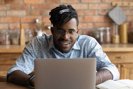 Photo pour Stunned young African American man in glasses look at laptop screen shocked by unexpected sale deal or offer online. Stunned biracial male surprised by unbelievable news or email on computer. - image libre de droit