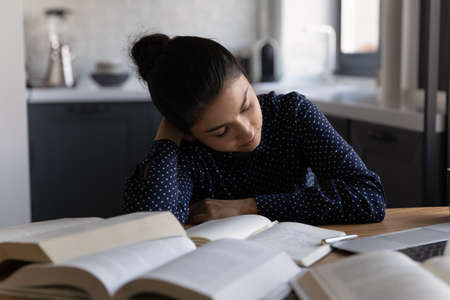 Photo pour Tired millennial ethnic female college or university student fall asleep at desk studying preparing for test. Exhausted young Indian woman sleep on table overwhelmed with homework. Education concept. - image libre de droit