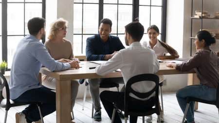 Foto de Smiling diverse multiracial businesspeople sit at desk in office discuss ideas at meeting together. Happy multiethnic colleagues have fun laugh brainstorming in group at briefing. Teamwork concept. - Imagen libre de derechos