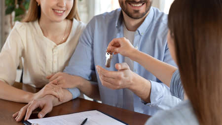 Happy houseowners. Close up of female real estate agent, broker or realtor holding in hand bunch of keys of new house flat apartment.
