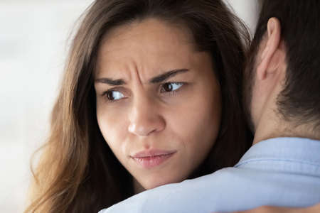 Foto de Close up view of frustrated young woman hugging husband and looking aside trying but having no power to forgive cheating lie betrayal - Imagen libre de derechos