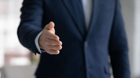 Photo pour Close up crop image young businessman reaching out hand for shaking, proposing good deal to partner, making greeting gesture to client, welcoming new employee at work, congratulating with achievement. - image libre de droit
