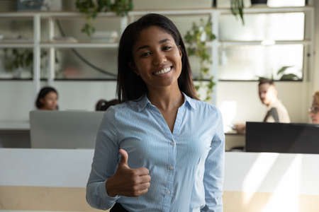 Foto de Portrait of happy smiling young asian woman employee showing thumb up gesture looking at camera expressing loyalty trust to her company, satisfied female client customer recommending goods or service - Imagen libre de derechos
