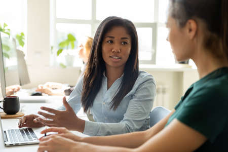 Photo for Internship. Attentive focused mixed race woman mentor trainer sitting by laptop at workplace explaining telling young caucasian female new hired employee trainee intern principles of corporate working - Royalty Free Image