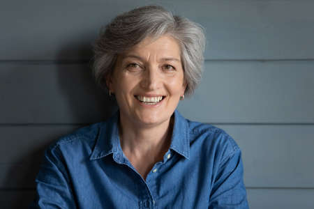 Photo pour Head shot portrait smiling grey haired mature woman standing posing on grey wooden wall background, attractive happy excited senior female with healthy skin and toothy smile looking at camera - image libre de droit