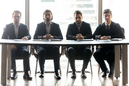 Photo pour Portrait of serious businessmen sit at desk in office show confidence and leadership at workplace. Concentrated male employers executives ready for business interview. Employment, success concept. - image libre de droit
