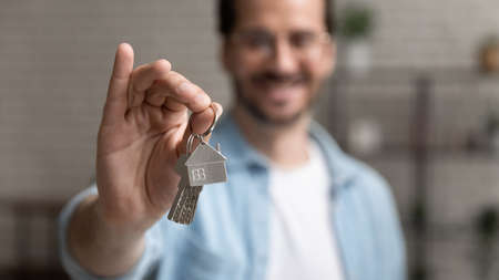 Photo pour Close up focus on keys with keychain in the form of house in male hands, happy young man homeowner purchased new apartment, feeling excited of moving in new flat, tenancy accommodation concept. - image libre de droit