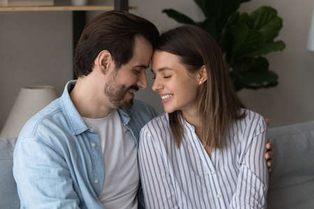 Photo pour Smiling young Caucasian couple sit relax on couch at home enjoy close tender romantic moment together. Happy millennial man and woman rest on sofa hug embrace show love and care. Relations concept. - image libre de droit