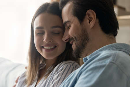 Photo pour Close up of happy young Caucasian couple hug embrace enjoy tender close intimate moment together. Smiling millennial man and woman spouses cuddle have romance indoors, show love and care. - image libre de droit