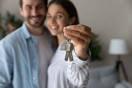 Crop close up of excited young Caucasian couple show keys to new shared home or dwelling. Happy man and woman spouses feel overjoyed moving relocating to own house. Rental, real estate concept.
