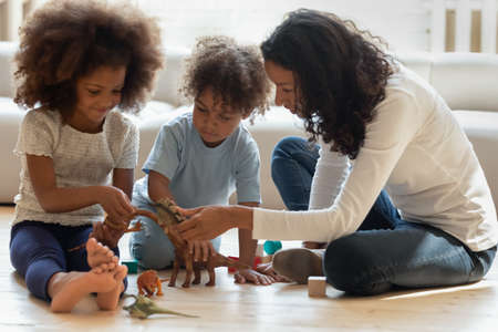Photo pour Jurassic period. Pleasant young black mother, female tutor or nanny sitting on warm floor involved in playing education game with two little african children telling interesting facts about dinosaurs - image libre de droit