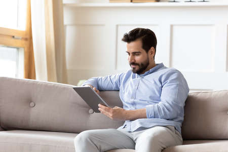 Photo pour Young Caucasian man renter sit rest on cozy couch in living room look at tablet screen browsing wireless internet. Millennial male tenant relax on sofa at home text message on pad gadget online. - image libre de droit