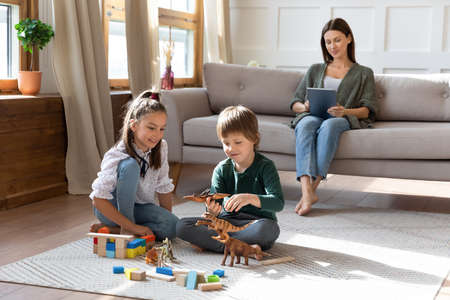 Photo pour Happy two little siblings children relax on warm floor in cozy living room play toys together, mom relax on couch with tablet. Smiling kids engaged in game, mother rest using pad device at home. - image libre de droit