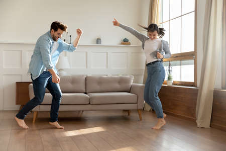 Photo for Happy millennial Caucasian couple renters dance celebrate relocation to new own apartment together. Overjoyed young husband and wife man and woman have fun enjoy weekend at home. Moving concept. - Royalty Free Image