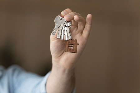 Crop close up of man hold show keys to own house buying first home from real estate agent. Male renter or buyer celebrate relocation moving to new home, make investment. Rent, realty concept.