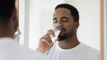 Photo pour Mirror reflection young peaceful african ethnicity mixed race man in white t-shirt drinking glass of fresh pure mineral water, hydrating organism in morning, enjoying daily healthcare habit at home. - image libre de droit