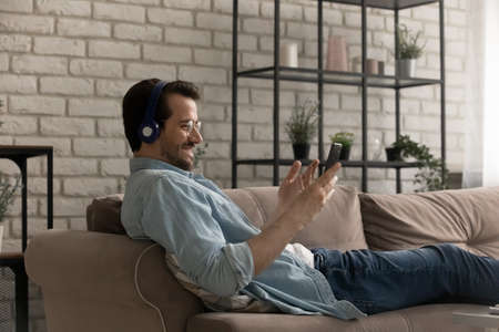Photo for Alone on weekend. Happy young male enjoying rest on cozy couch playing mobile game in wireless headphones. Content man listen music from smartphone playlist or choose audio book at online library - Royalty Free Image