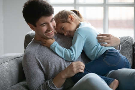 Photo pour Close up happy father and little daughter cuddling and hugging, sitting on cozy couch at home, smiling loving dad and adorable preschool girl child enjoying weekend together, playing funny game - image libre de droit