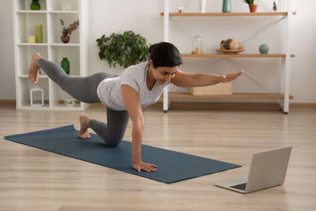 Foto de Active young female of indian ethnicity enjoy yoga at home practice static tiger asana. Mixed race woman trainee having personal fitness class online look at laptop screen imitate instructor movements - Imagen libre de derechos