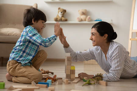 Photo pour We are great team. Laughing indian mommy give high five to happy kid son celebrate building of high brick tower. Female babysitter construct from brick set with small boy on floor with heating system - image libre de droit