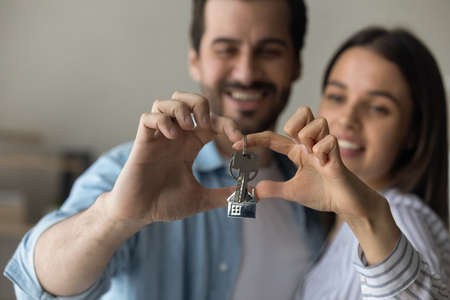 Photo pour Love lives here. Happy caring millennial family couple posing at new home house cuddling making heart shape of fingers with bunch of keys inside. Focus on joined hands of spouses holding key. Close up - image libre de droit