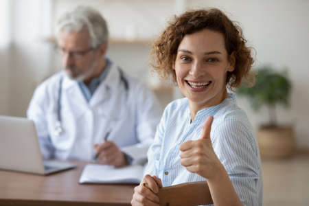 Photo for Overjoyed young Caucasian female patient show thumb up satisfied with consultation with doctor. Smiling woman client satisfied recommend good quality service in hospital. Recommendation concept. - Royalty Free Image