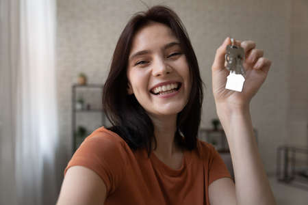 Photo pour Starting new life. Overjoyed young female hold keys from new home look at camera shoot selfie portrait to share news at social network. Excited millennial lady proud of becoming homeowner first time - image libre de droit