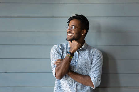 Photo pour Bearded dreamer. Smiling millennial afro american man hipster in stylish glasses posing against grey wall look away. Confident motivated young black guy dream think feel hopeful optimistic. Copy space - image libre de droit