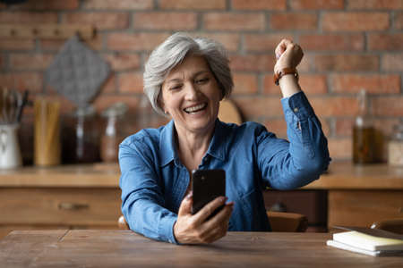 Photo pour Overjoyed aged senior latin grandmother pensioner yell yes super celebrate winning mobile phone game. Happy elderly female sit at kitchen table read email excited with great sale discount at web shop - image libre de droit