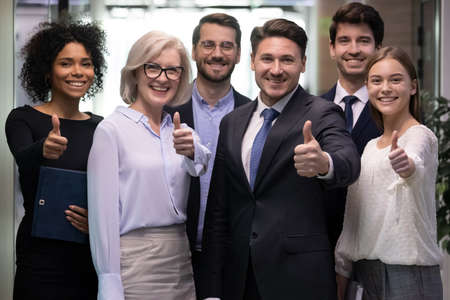Photo pour Portrait of smiling multiethnic team show thumbs up give recommendation to good quality service. Happy diverse multiracial businesspeople recommend company or bank experience. Employment concept. - image libre de droit