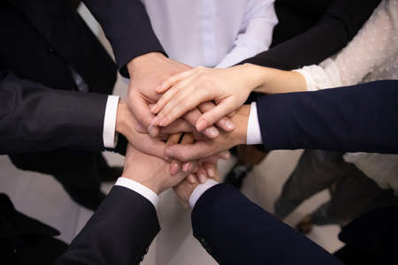 Photo pour Crop close up top view of multiracial employees colleagues stack hands in pile show team loyalty and unity. Diverse multiethnic businesspeople engaged in teambuilding activity. Teamwork concept. - image libre de droit