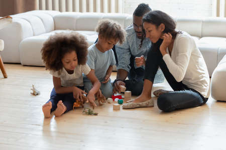 Photo pour African American parents and two preschooler kids playing toy blocks and dinosaurs on heat floor in living room. Happy family enjoying weekend leisure time at home. Couple engaged in children playtime - image libre de droit