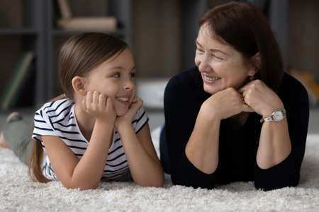 Photo pour Smiling mature 60s Caucasian grandmother and cute little teenage granddaughter relax lie on carpet in living room. Happy loving elderly granny and small teen girl child have fun rest together at home. - image libre de droit