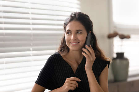 Photo pour Good talk. Happy young hispanic woman standing by window at home speak keep conversation holding telephone to ear. Positive millennial latina female spend free time calling friend chatting gossiping - image libre de droit
