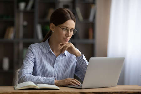 Foto de Online business. Focused young lady in glasses sit at home office engaged in computer job read information on laptop screen. Thoughtful millennial woman chat in corporate network type email text on pc - Imagen libre de derechos