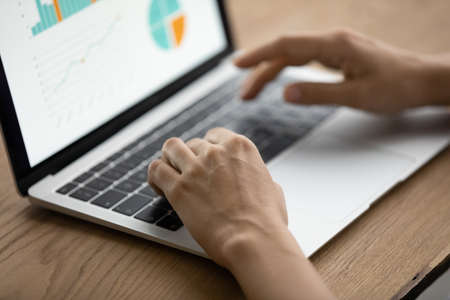Photo pour Managing project performance. Close up of woman manager hands type on laptop keyboard prepare business analytic report via online service. Marketing specialist work with sales infographic on pc screen - image libre de droit