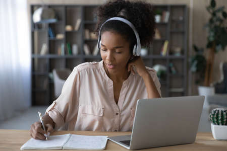 Photo pour Happy young african american woman in wireless headphones listening educational online lecture, writing down important information. Smart mixed race student involved in online study by video zoom call - image libre de droit