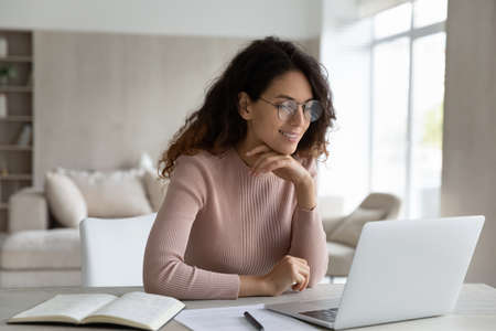 Photo pour Happy Hispanic woman in glasses sit at desk work online on laptop make notes handwrite. Smiling Latino female student study on web on computer, take distant course or training on gadget at home. - image libre de droit