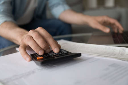 Photo pour Close up young man managing household budget, calculating domestic expenditures, planning investments or managing savings earnings, paying bills or taxes, financial affairs, accounting concept. - image libre de droit