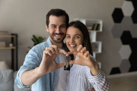 Photo pour Happy sincere young family couple showing keys to camera, feeling excited of moving into new renovated apartment. Smiling man woman spouses satisfied with real estate agency service, tenancy concept. - image libre de droit