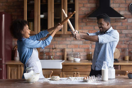 Photo pour Happy young African American man and woman spouses have fun fight on kitchen appliances cooking together at home. Smiling millennial ethnic couple laugh baking preparing food. Hobby concept. - image libre de droit