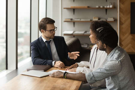 Photo pour Caucasian family financial advisor consulting to young 30s African couple during meeting in bank office. Realtor communicates to spouses about tenancy. Loan and mortgage, real estate purchase concept - image libre de droit