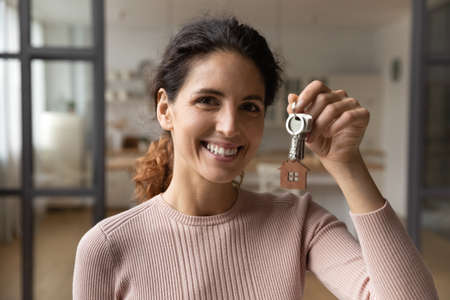 Photo pour Headshot portrait of happy millennial female tenant or renter relocate show keys to new own home. Profile picture of smiling young Caucasian woman celebrate buy first house. Rental, moving concept. - image libre de droit