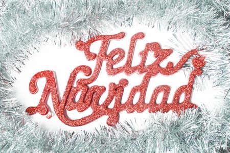 Adornos de feliz navidad en español, las letras en rojo y guirnaldas en plata.
